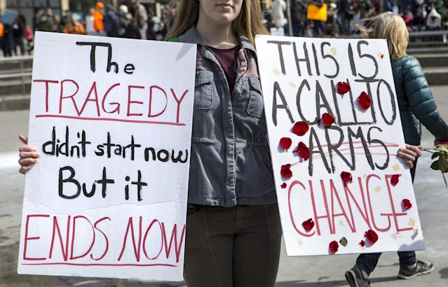 <p>An attendee holds two signs at the March for Our Lives 2018 event in Grand Rapids, Michigan, on Saturday, March 24, 2018. (Casey Sykes | MLive.com/AP) </p>