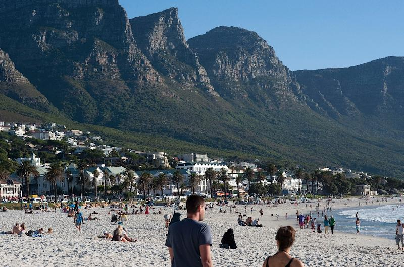 People walk on the beach in the upmarket suburb of Camps Bay, one of the most popular tourist destinations in Cape Town, on January 11, 2014