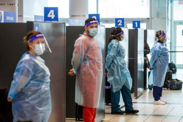 Health-care workers prepare to test passengers as they arrive at Toronto's Pearson airport in this Feb. 1, 2021 photo after mandatory COVID-19 testing took effect for international arrivals. Public Health Ontario said Friday it has detected 36 cases of the B1617 variant first identified in India. (Carlos Osorio/Reuters - image credit)