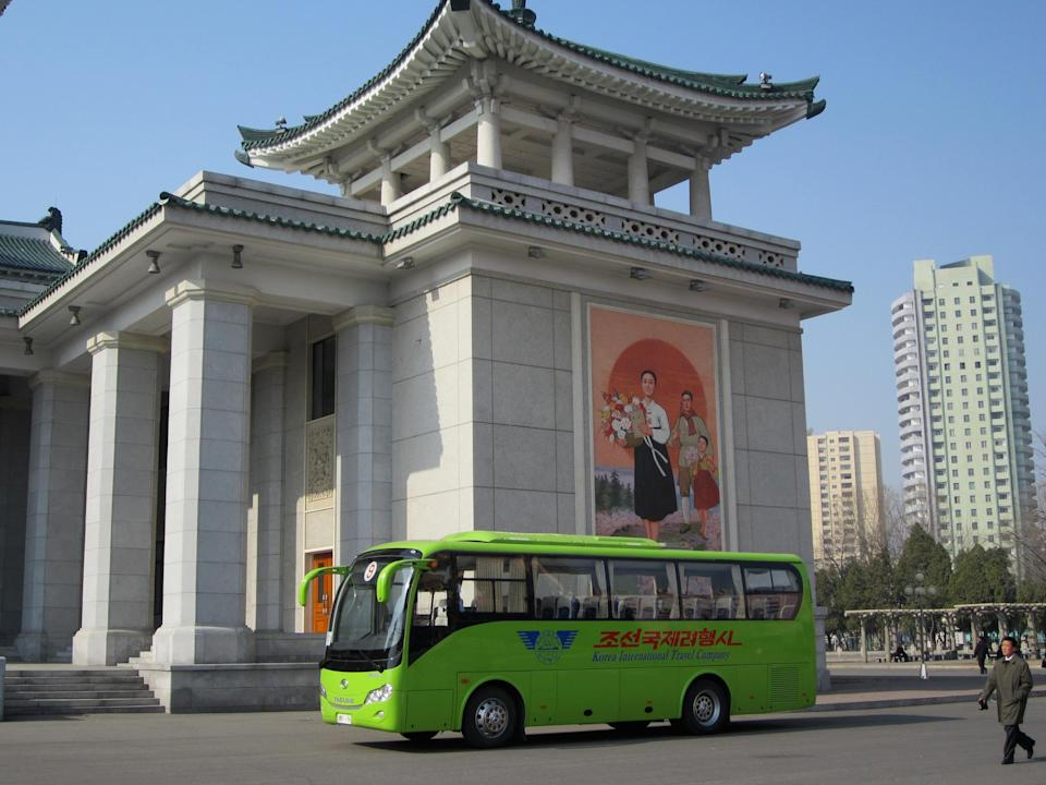 """Our bus outside the Pyongyang Grand Theater, which stages such revolutionary extravaganzas as """"Sea of Blood"""" and """"True Daughter of the Party."""" Our two guides explain what we may NOT photograph: anyone in military uniform (about a third of the population), any statues or portraits of the Great Leader or the Dear Leader, unless they are full body shots. (So no cropping off arms, legs, or other parts, which is rude and disrespectful.)"""