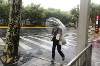 A woman carrying an umbrella braces against the wind and rain as Typhoon In-fa sweeps through Shanghai in China Sunday, July 25, 2021. Typhoon In-fa hit China's east coast south of Shanghai on Sunday after people living near the sea were evacuated, airline flights and trains were canceled and the public was ordered to stay indoors. (AP Photo/Chen Si)