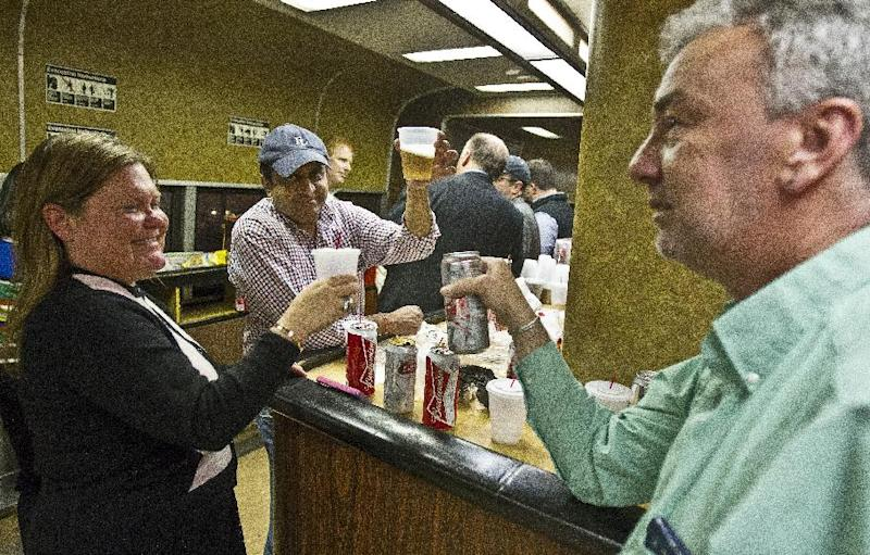 Nan Buziak Lexow, left, Srikanth Reddy, center, and Mark DeMonte, right, raise a toast while riding the bar car on the 7:07 p.m. train from Grand Central Terminal in New York to New Haven, Conn., Thursday, May 8, 2014. The trio toasted the bar car, being retired from Metro-North's New Haven Line after Friday's afternoon rush hour. The cars were a fixture on Metro-North Railroad trains for at least a half century. The cars, decked out with orange walls and faux wood paneling, are being retired Friday, because they cannot be coupled to the new fleet of train cars on the New Haven line. (AP Photo/Michael R. Sisak)