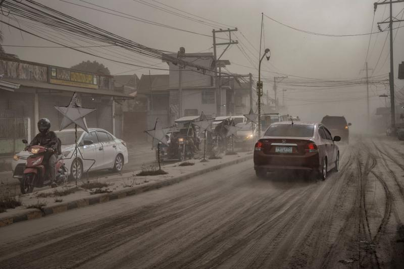 Motorists drive through a road covered in volcanic ash from Taal Volcano's eruption in Lemery, Batangas province, Philippines on Jan. 13, 2020. | Ezra Acayan—Getty Images