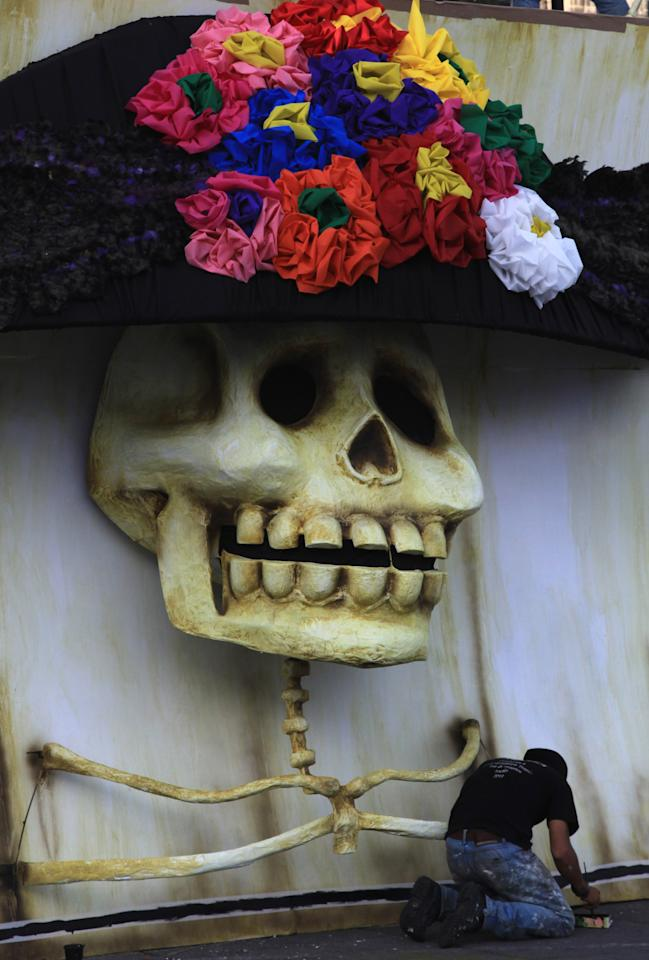 "An artist paints a traditional Mexican ""Catrina"" as part of the Day of the Dead celebrations in Mexico City's Zocalo, Wednesday, Oct. 30, 2013. Mexicans celebrate Day of the Dead to honor deceased loved ones, a tradition that coincides with All Saints Day and All Souls Day on Nov. 1 and 2. (AP Photo/Marco Ugarte)"