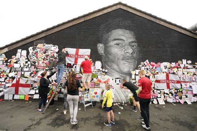 People put up flags and messages on the mural of Manchester United striker and England player Marcus Rashford on the wall of the Coffee House Cafe on Copson Street, Withington, after it had been defaced