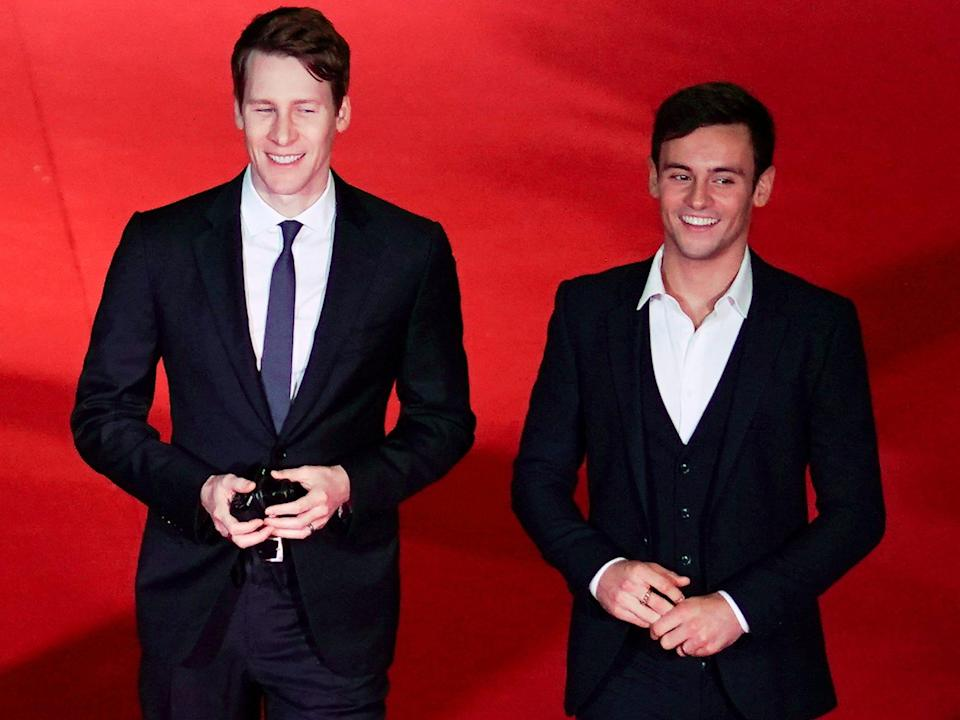 Dustin Lance Black and Tom Daley in 2017 in suits on a red carpet