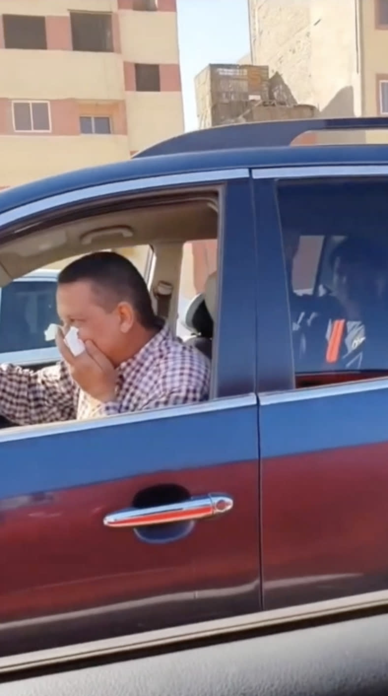 Pictured is a taxi driver covering his face with a tissue as his Chinese passenger sits in the back seat.