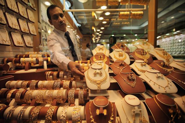 DUBAI, UNITED ARAB EMIRATES - DECEMBER 03: A man arranges gold in a shop window in the gold souk on December 3, 2009 in Dubai, United Arab Emirates. Stock markets in the Dubai and Abu Dhabi fell sharply this week after state owned company Dubai World asked for more time to pay off depts, amounting to 35Bn GBP. The Dubai economy which has enjoyed years of rapid growth has seen a sharp decline recently as world markets reacted to the global economic crisis. (Photo by Dan Kitwood/Getty Images)