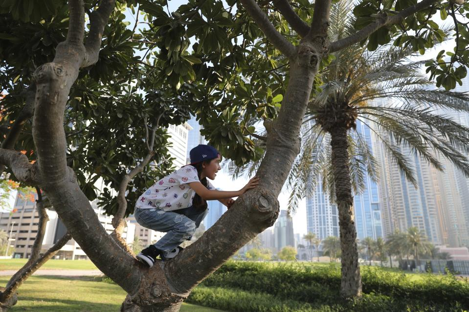 Michelle Rasul climbs a tree at a park near her house in Dubai, United Arab Emirates, Sunday, May 9, 2021. Rasul, a 9-year-old girl from Azerbaijan who lives in Dubai, is scratching her way to the top as a DJ after competing in the DMC World DJ Championship. (AP Photo/Kamran Jebreili)