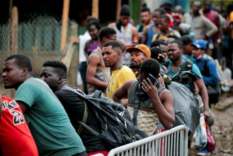 Migrants queue up to register their official entry into Panama at the village of Bajo Chiquito, close to the border with Colombia