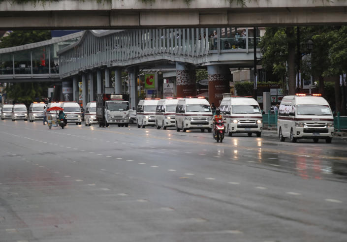 Vehicles carry police taking position in a business district where anti-government protesters sayid they will meet in Bangkok, Thailand, Friday, Oct. 16, 2020. Police announced Friday they would block roads leading to Bangkok's Rajprasong intersection, where Thursday's rally was held, after protesters called on supporters to mass again. (AP Photo/Sakchai Lalit)