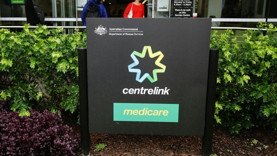 Centerlink and Medicare signage in front of a hedge.