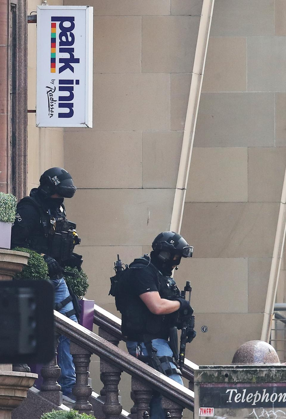 Armed police officers leave the Park Inn hotel in West George Street, Glasgow, after a suspect male was shot by an armed officer. (PA)