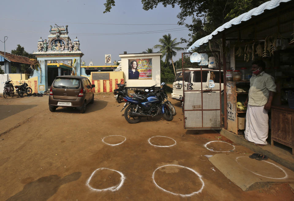 Markings are seen next to a grocery store for maintaining social distance outside a temple displaying a banner featuring U.S. democratic vice presidential candidate Sen. Kamala Harris in Thulasendrapuram village, south of Chennai, Tamil Nadu state, India, Tuesday, Nov. 3, 2020. The lush green village is the hometown of Harris' maternal grandfather who migrated from there decades ago. (AP Photo/Aijaz Rahi)