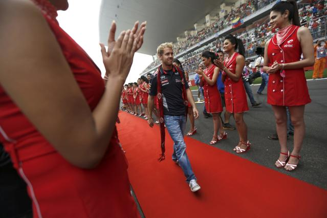 Grid girls clap as Red Bull Formula One driver Sebastian Vettel of Germany walks on a red carpet during the Indian F1 Grand Prix at the Buddh International Circuit in Greater Noida, on the outskirts of New Delhi, October 27, 2013. REUTERS/Ahmad Masood (INDIA - Tags: SPORT MOTORSPORT F1)
