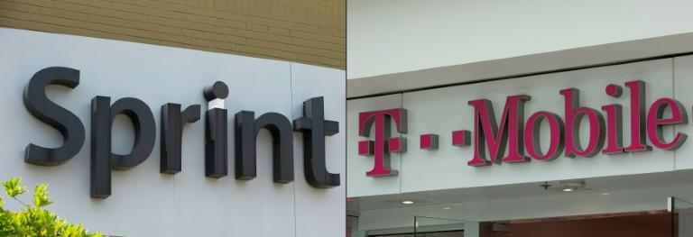 Wireless carriers T-Mobile and Sprint moved a step closer to merging, winning the approval of the Federal Communications Commission for their $26 billion tie-up