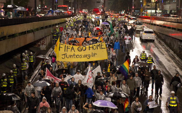Demonstrators march to protest the amount of money spent on World Cup preparations in Sao Paulo, Brazil, Tuesday, April 15, 2014. Brazil will host the soccer tournament this year. (AP Photo/Andre Penner)