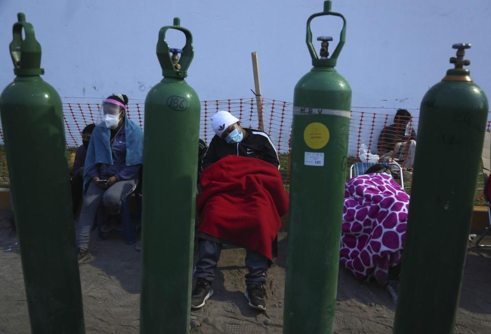 People sleep framed by their empty oxygen cylinders waiting for a shop to open to refill their tanks, in the Villa El Salvador neighborhood of Lima, early Thursday morning, Feb. 18, 2021. A crisis over the supply of medical oxygen for coronavirus patients has struck nations in Africa and Latin America, where warnings went unheeded at the start of the pandemic and doctors say the shortage has led to unnecessary deaths. (AP Photo/Martin Mejia)