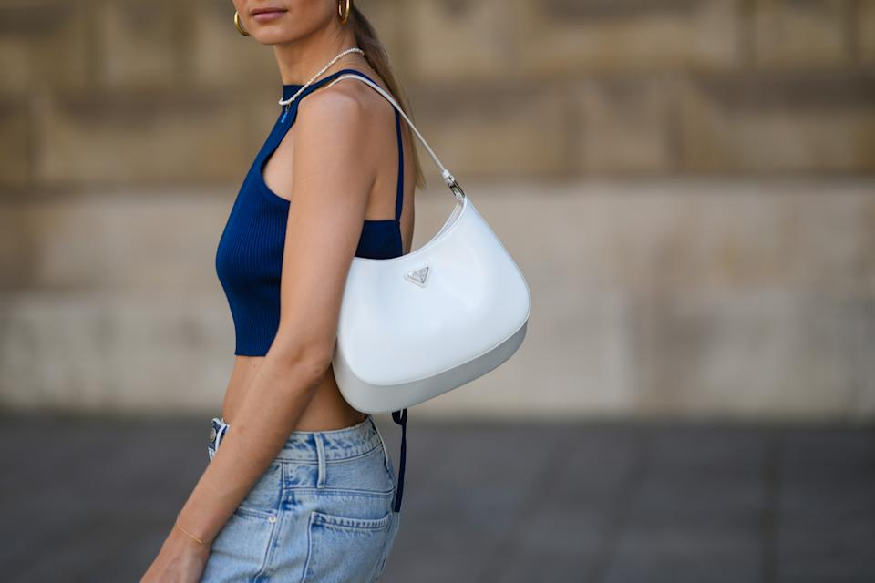 PARIS, FRANCE - JUNE 11: Xenia Adonts wears golden earrings, a beaded necklace, a blue off-shoulder back-nude cropped tank top, pale blue wide-leg flared ripped denim jeans pants, a white leather Cleo Prada bag, on June 11, 2021 in Paris, France. (Photo by Edward Berthelot/Getty Images)