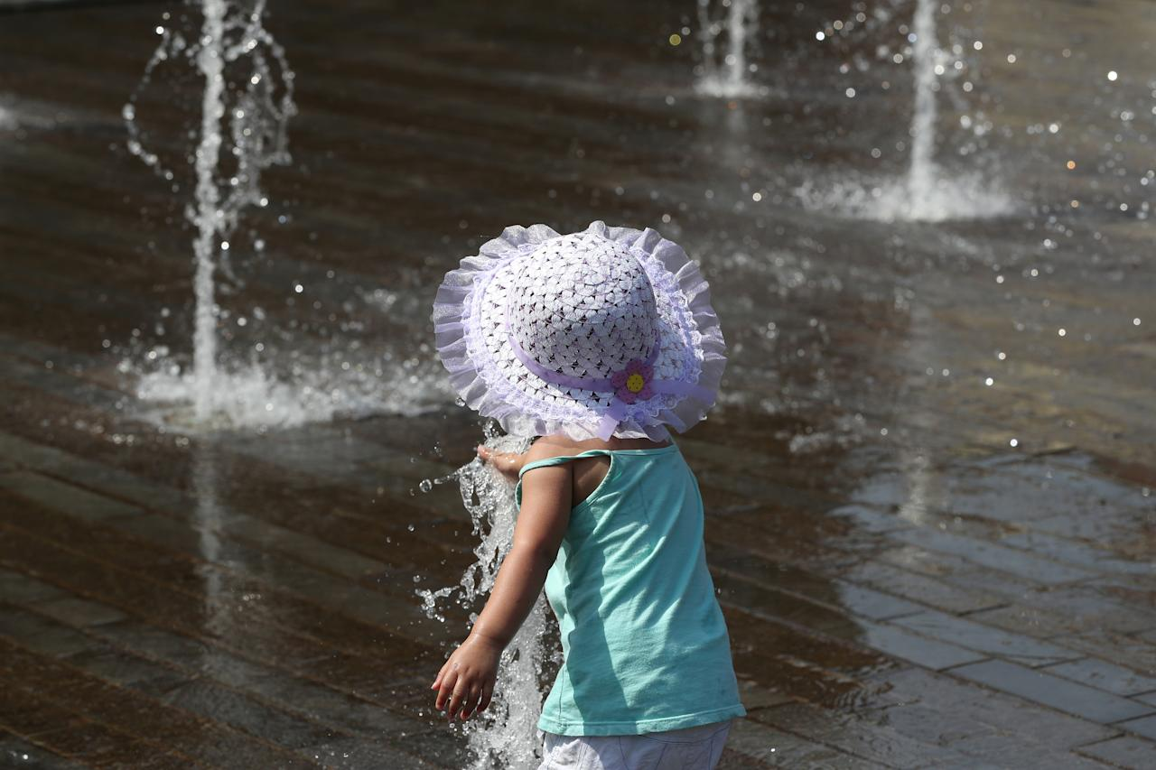 A girl plays with water in a fountain on a hot summer day in Brussels, Belgium, July 24, 2019. REUTERS/Yves Herman