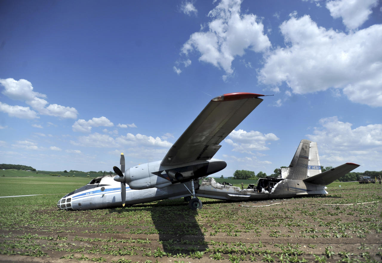 An AN-30 military aircraft lies off the runway at the Czech air force base in Caslav, some 20 miles east of Prague, Wednesday, May 23, 2012. An official says the Russian military plane caught fire after problems during the landing maneuver, injuring at least six people on board. Czech military spokeswoman Jana Ruzickova said the plane had 23 people on board, 14 Russians and 9 Czechs. Five Russians and one Czech national have suffered injuries, mostly burns. The plane and Russian officials were in the Czech Republic on a regular monitoring mission. (AP Photo/CTK, Josef Vostarek) SLOVAKIA OUT
