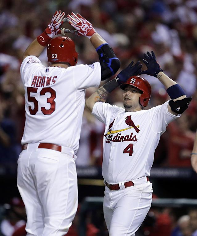 St. Louis Cardinals' Matt Adams (53) celebrates with Yadier Molina (4) as Adams crosses home plate after hitting a two-run home run against the Pittsburgh Pirates in the eighth inning in Game 5 of a National League baseball division series on Wednesday, Oct. 9, 2013, in St. Louis. The Cardinals won the game 6-1and won the series 3 games to 2.(AP Photo/Charlie Riedel)