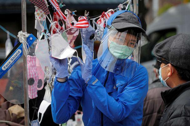 PHOTO: A man speaks to a street vendor about face masks, during the outbreak of the coronavirus disease, in the Queens borough of New York, May 19, 2020. (Brendan Mcdermid/Reuters)
