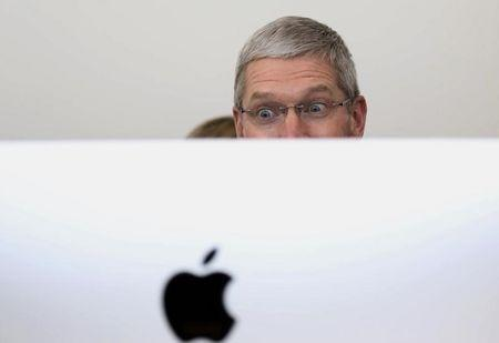 Apple CEO Tim Cook looks at a new IMac after a presentation at Apple headquarters in Cupertino, California October 16, 2014.  REUTERS/Robert Galbraith