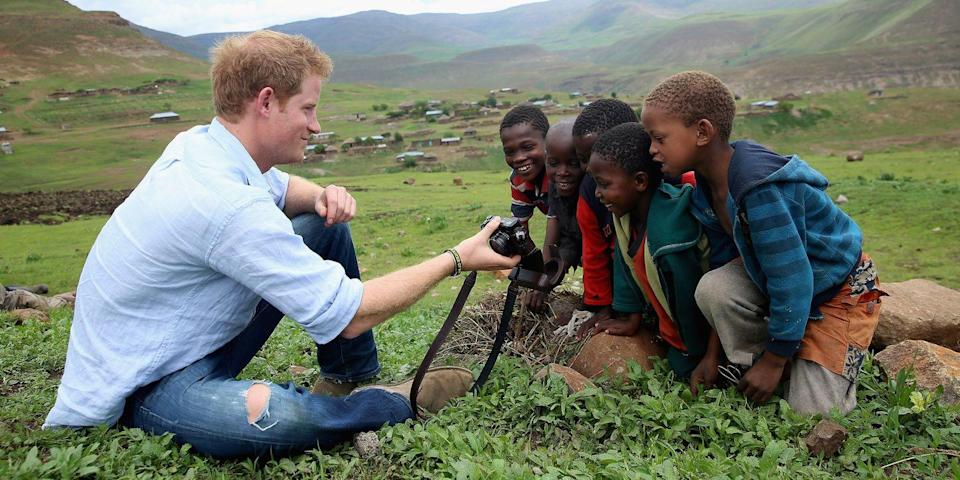<p>Harry takes photos with local kids while on a trip to Mokhotlong, Lesotho. </p>