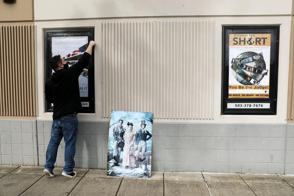 Marcus Salem changes the movie poster at Salem Cinema in Oregon on Wednesday.The sun-bleached posters haven't been changed since March, when the theater shut down because of the coronavirus pandemic.