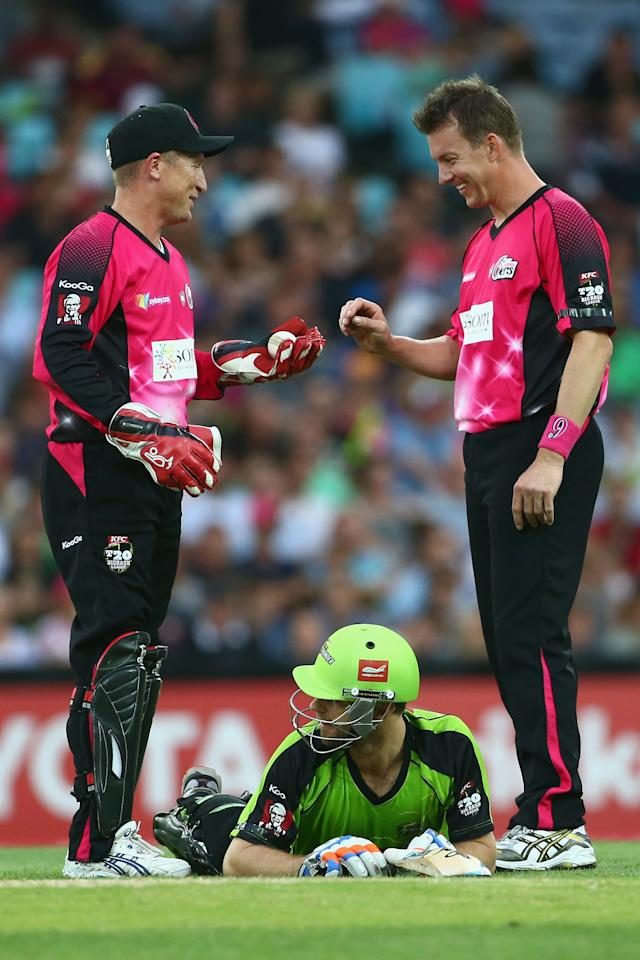 SYDNEY, AUSTRALIA - DECEMBER 30:  Brad Haddin and Brett Lee of the Sixers share a laugh as Ryan Carters of the Thunder lies on the ground during the Big Bash League match between Sydney Thunder and the Sydney Sixers at ANZ Stadium on December 30, 2012 in Sydney, Australia.  (Photo by Mark Kolbe/Getty Images)