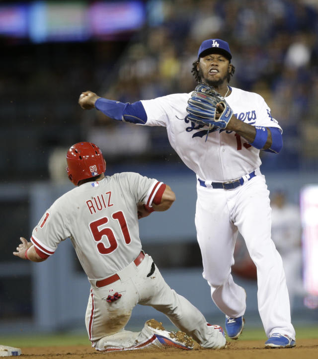 Los Angeles Dodgers shortstop Hanley Ramirez, right, throws to first base to complete a double play after forcing out Philadelphia Phillies' Carlos Ruiz during the seventh inning of a baseball game on Thursday, April 24, 2014, in Los Angeles. Philadelphia Phillies' Ryan Howard was out at first. (AP Photo/Jae C. Hong)
