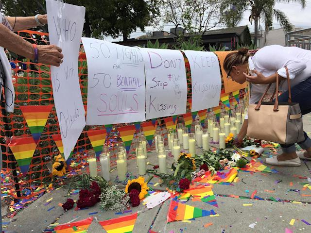 <p>People tend to a memorial at the Christopher Street West presentation of the Los Angeles LGBT Pride Parade in West Hollywood, Calif., June 12, 2016 in honor of the victims of the deadly attacks at a gay night club in Orlando, Florida earlier in the morning. (REUTERS/Lisa Richwine) </p>