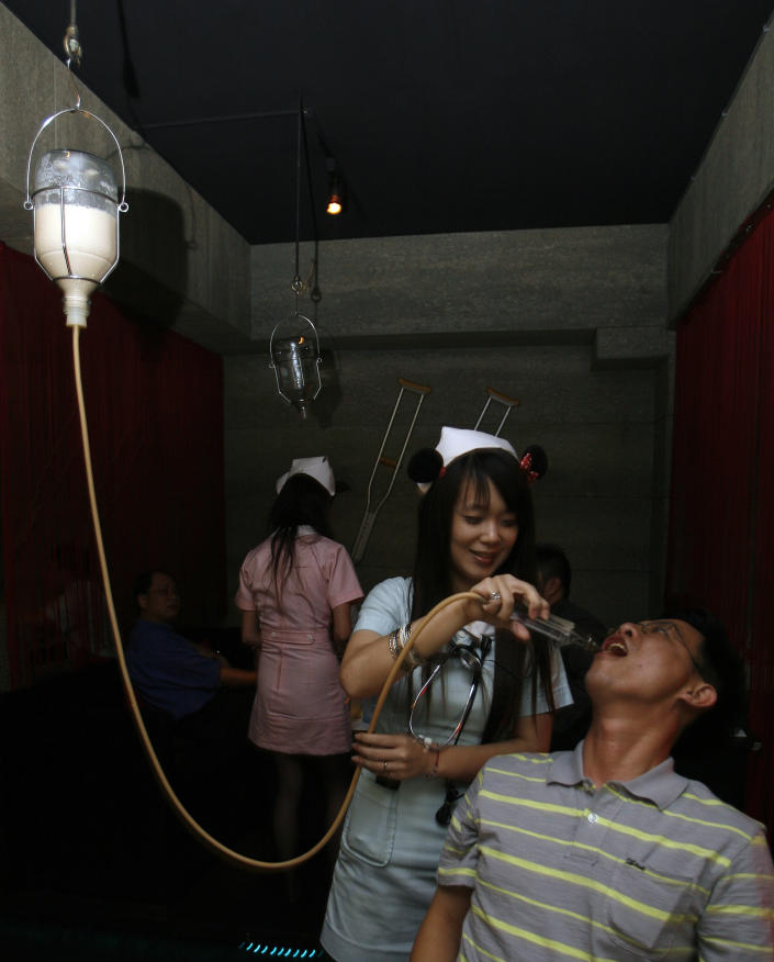 A waitress dressed in a nurse uniform serves a drink to a customer with a drip at a hospital-themed restaurant in Taipei March 18, 2009. REUTERS/Nicky Loh