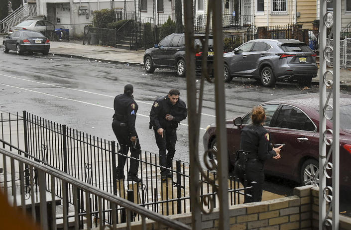 In this Dec. 10, 2019 photo, Jersey City police Sgt. Marjorie Jordan, left, helps fellow officer Raymond Sanchez to safety after he was shot during a gunfight that left multiple dead in Jersey City, N.J. The two killers were armed with a variety of weapons, including an AR-15-style rifle and a shotgun that they were wielding when they stormed into a store in an attack that left the scene littered with several hundred shell casings, broken glass and a community in mourning. Despite years of New Jersey officials focusing on the problems of crime guns coming into the state, Tuesday's shooting shows efforts are falling short. (Justin Moreau via AP)