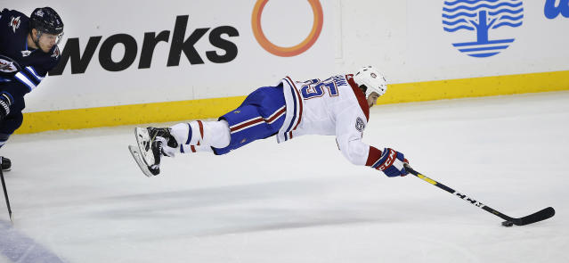 Montreal Canadiens' Andrew Shaw (65) plays the puck after getting tripped by Winnipeg Jets' Dmitry Kulikov (5) during the third period of an NHL hockey game Saturday, March 30, 2019 in Winnipeg, Manitoba. (John Woods/The Canadian Press via AP)