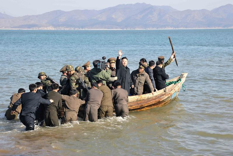 FILE - In this March 11, 2013 file photo released by the Korean Central News Agency (KCNA) and distributed by the Korea News Service, North Korean leader Kim Jong Un waves at military officers after inspecting the Wolnae Islet Defense Detachment, North Korea, near the western sea border with South Korea. For the outside world, North Korea's message is largely doom and gloom: bombastic threats of nuclear war, fantasy videos of U.S. cities in flames, digitally altered photos of military drills. But a domestic audience gets a parallel and decidedly softer dose of propaganda - and one with potentially higher stakes for the country's young leader. (AP Photo/KCNA via KNS, File)