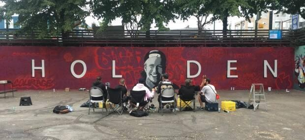 A mural dedicated to late graffiti artist Holden Courage, covering a 20-metre concrete wall in a parking lot in East Vancouver, is shown in 2018. The background of the mural is covered in reproductions of Holden's own graffiti recreated by some of his closest friends. (taramcguire.com - image credit)