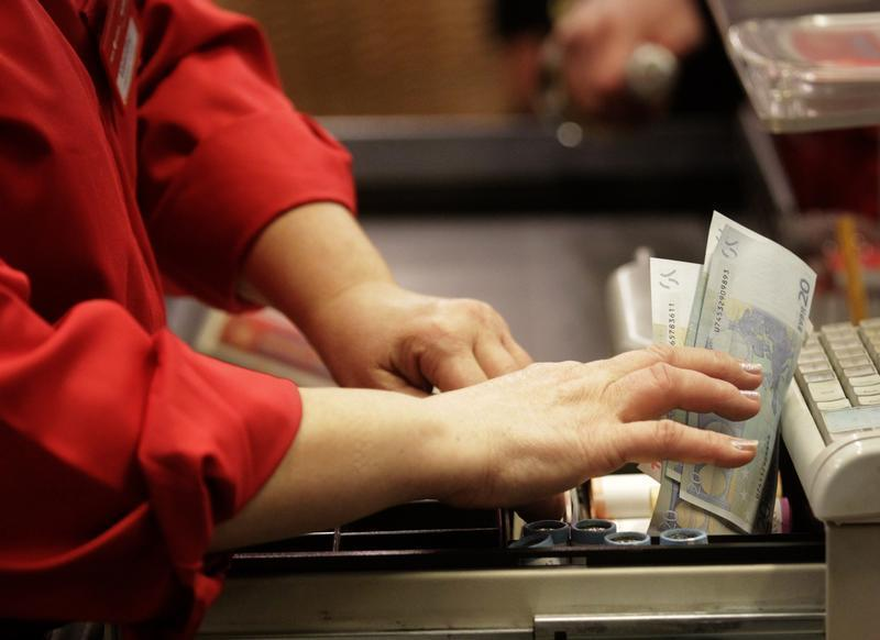 A cashier holds euro banknotes in Riga