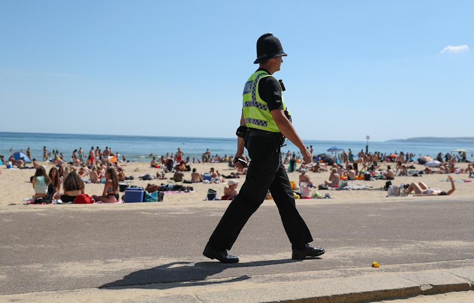 A police officer patrols along the beach in Bournemouth, Dorset, as the public are being reminded to practice social distancing following the relaxation of the coronavirus lockdown restrictions in England. (Photo by Andrew Matthews/PA Images via Getty Images)
