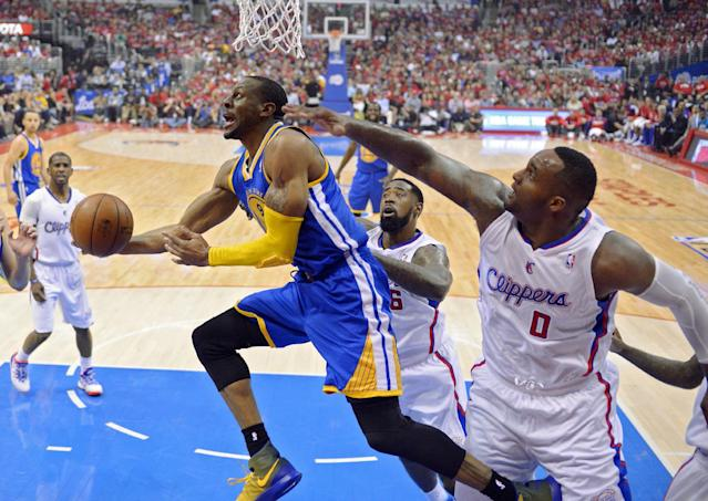 Golden State Warriors forward Andre Iguodala, left, puts up a shot as Los Angeles Clippers center DeAndre Jordan, center, and forward Glen Davis defend during the first half in Game 1 of an opening-round NBA basketball playoff series, Saturday, April 19, 2014, in Los Angeles. (AP Photo/Mark J. Terrill)