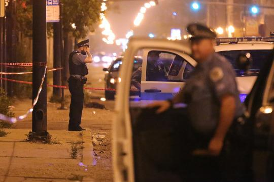 A police officer rests his hand on his forehead at the scene where a 23-year-old man was shot in the face on July 6, 2015, in Chicago. (Photo: Anthony Souffle/Chicago Tribune/TNS via Getty Images)