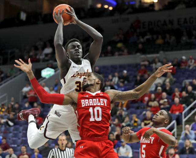 Loyola of Chicago's Aher Uguak is unable to come down with a rebound over Bradley's Elijah Childs (10) and Darrell Brown (5) during the first half of an NCAA college basketball game in the semifinal round of the Missouri Valley Conference tournament, Saturday, March 9, 2019, in St. Louis. (AP Photo/Jeff Roberson)