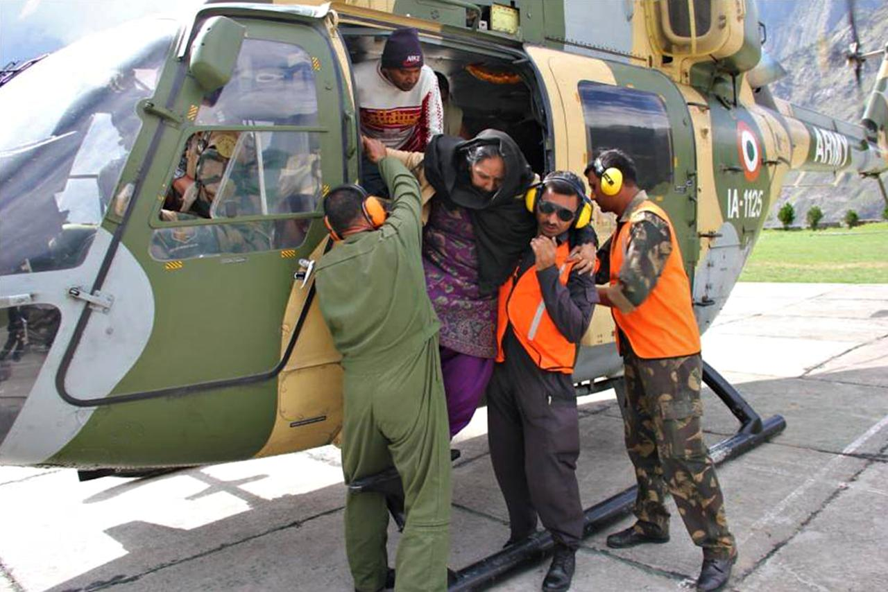 "In this photograph received from the Indian Army on June 20, 2013, members of the Indian Defence Forces assist an evacuee out of a helicopter following flash floods in the northern Uttarakhand state. India's military battled on June 20 to reach villages and towns cut off by flash floods and landslides in the country's north as officials warned at least 1,000 people may have been killed. AFP PHOTO/INDIAN ARMY   ----EDITORS NOTE---- RESTRICTED TO EDITORIAL USE - MANDATORY CREDIT -  ""AFP PHOTO/INDIAN ARMY"" - NO MARKETING NO ADVERTISING CAMPAIGNS - DISTRIBUTED AS A SERVICE TO CLIENTS -----"