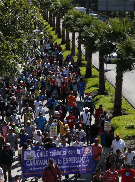 Scores of Central American migrants, representing the thousands participating in a caravan trying to reach the U.S. border, undertake an hours-long march to the office of the United Nations' humans rights body in Mexico City, Thursday, Nov. 8, 2018. Members of the caravan which has stopped in Mexico City demanded buses Thursday to take them to the U.S. border, saying it is too cold and dangerous to continue walking and hitchhiking.(AP Photo/Rebecca Blackwell)