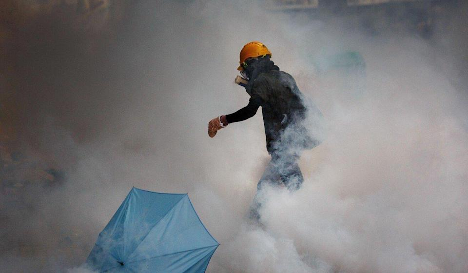 A demonstrator walks through a cloud of tear gas during a protest in Hong Kong against a proposed extradition law on June 12, 2019. Photo: Bloomberg