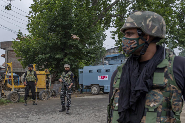 Indian paramilitary soldiers stand guard on a road leading towards the site of a gunfight in Pulwama, south of Srinagar, Indian controlled Kashmir, Wednesday, July 14, 2021. Three suspected rebels were killed in a gunfight in Indian-controlled Kashmir on Wednesday, officials said, as violence in the disputed region increased in recent weeks. Two residential houses were also destroyed. (AP Photo/ Dar Yasin)
