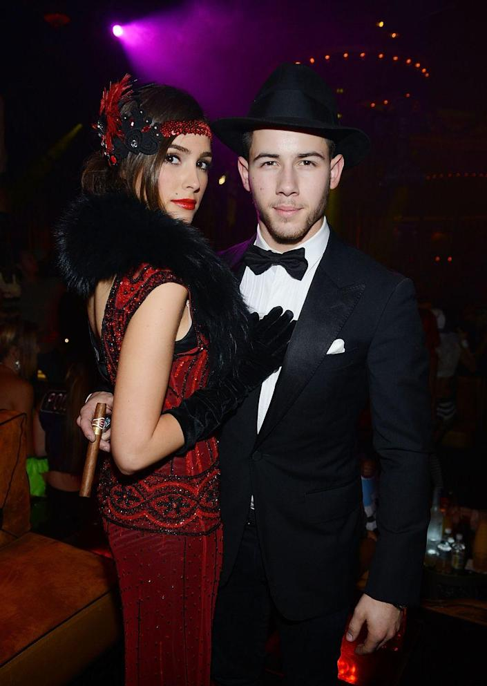"""<p>With the help of a sparkly dress and a sharp suit, you and your SO can transport yourself back to the roaring '20s as a flapper and a mobster. </p><p><a class=""""link rapid-noclick-resp"""" href=""""https://www.amazon.com/Meilun-Sequined-Inspired-Flapper-Evening/dp/B01N2QCS16?tag=syn-yahoo-20&ascsubtag=%5Bartid%7C10070.g.1923%5Bsrc%7Cyahoo-us"""" rel=""""nofollow noopener"""" target=""""_blank"""" data-ylk=""""slk:SHOP RED FLAPPER DRESS"""">SHOP RED FLAPPER DRESS</a></p><p><a class=""""link rapid-noclick-resp"""" href=""""https://www.amazon.com/Fedora-Hats-Unisex-Manhattan-Black/dp/B00EQWP8I2?tag=syn-yahoo-20&ascsubtag=%5Bartid%7C10070.g.1923%5Bsrc%7Cyahoo-us"""" rel=""""nofollow noopener"""" target=""""_blank"""" data-ylk=""""slk:SHOP BLACK FEDORA"""">SHOP BLACK FEDORA</a></p>"""