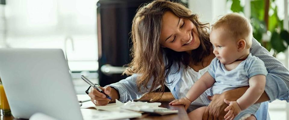 Young happy mother going through home finances and communicating with her baby son.