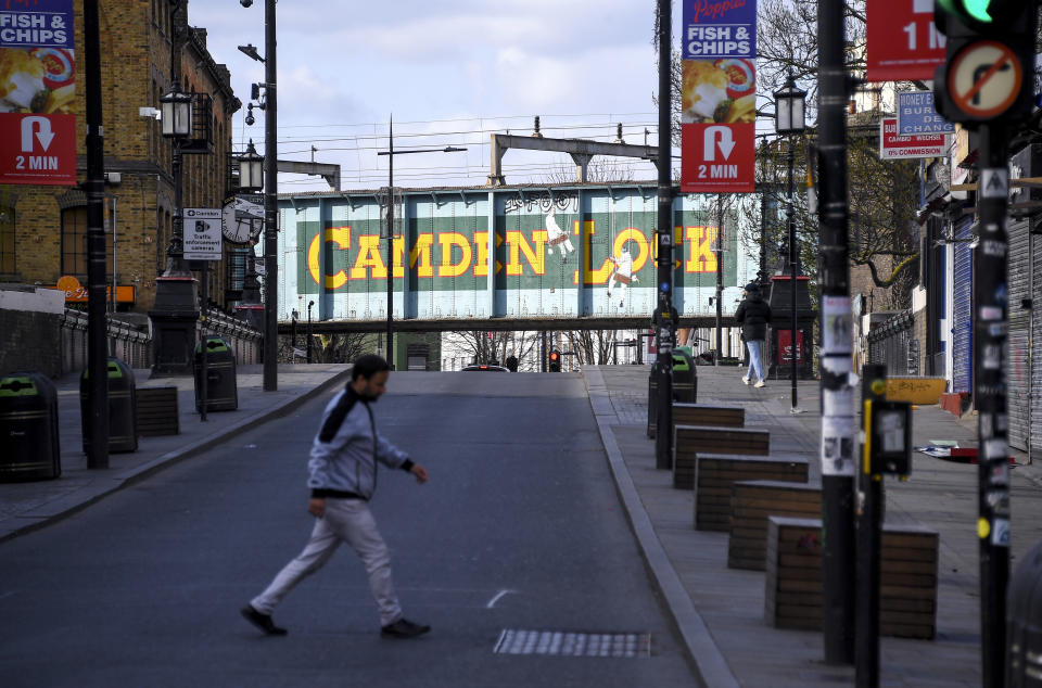 A man walks in an empty Camden High Street, due to the Coronavirus outbreak, in London, Sunday, March 29, 2020. The public have been asked to self isolate, keeping distant from others to limit the spread of the contagious COVID-19 coronavirus. The new coronavirus causes mild or moderate symptoms for most people, but for some, especially older adults and people with existing health problems, it can cause more severe illness or death. (AP Photo/Alberto Pezzali)